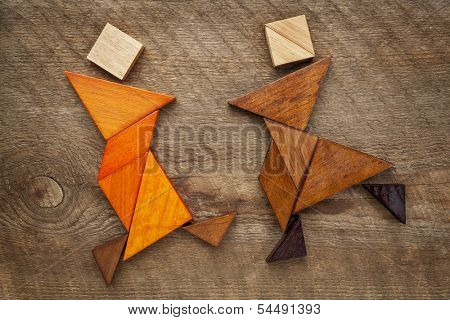 a couple of dancers or martial artists - abstract figures  built from tangram wooden pieces, a traditional Chinese puzzle game, artwork created by the photographer
