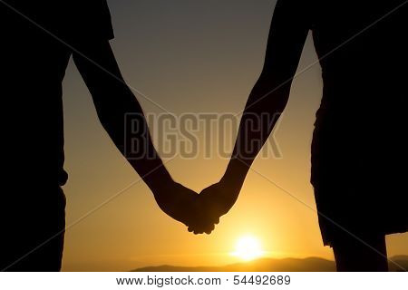 Holding Hands In Front Of Sunset