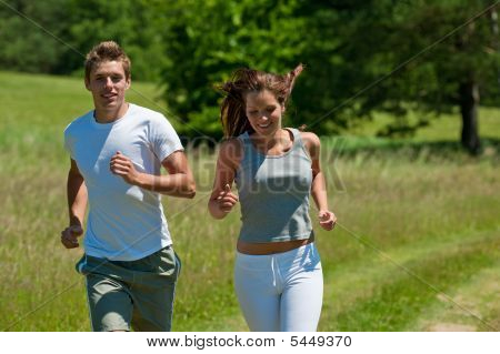 Young Man And Woman Running Outdoors