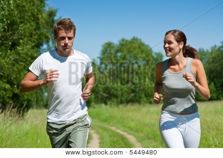 Sportive Man And Woman Jogging Outdoors