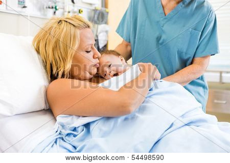 Medical professional assisting mother with skin to skin care in the hospital