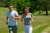 Young man and woman running outdoors shallow DOF poster