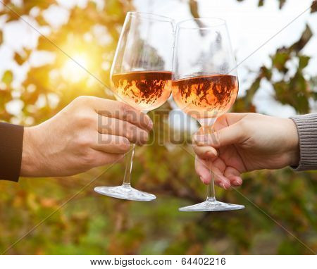 Young Happy Couple Enjoying A Glasses Of Pink Wine