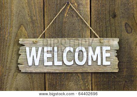 Wood welcome sign hanging on rustic door