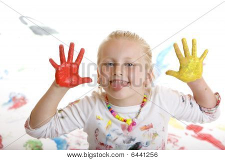Young handsome female child full of finger paint makeing a grimace