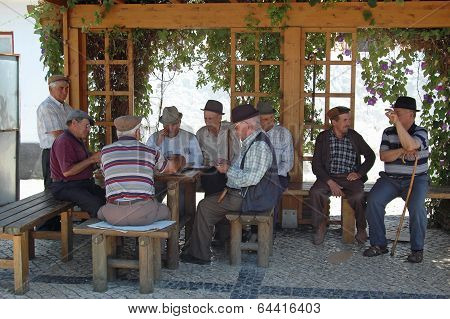 men sitting in a village in Portugal, playing cards