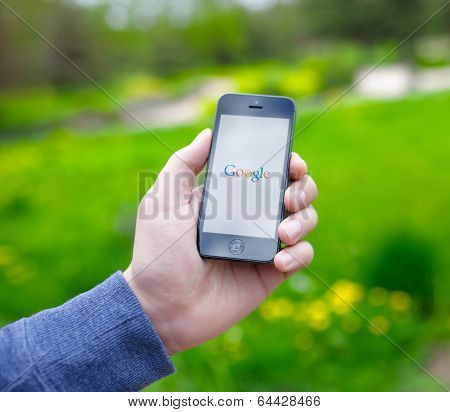 Male Hand Holding Iphone With Google On The Screen
