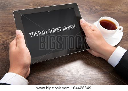 Businessman Holding Ipad With Wall Street Journal On The Screen