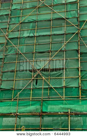 Construction Scaffolding And Green Debris Netting Abstract Background.