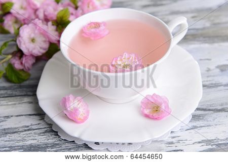Beautiful fruit blossom with cup of tea on table close-up