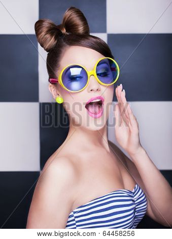 Attractive surprised young woman wearing sunglasses on checkered background, beauty and fashion concept