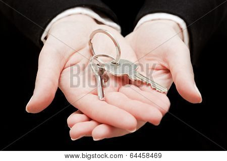 A real estate agent holding keys to a new house in her hands. Real estate industry