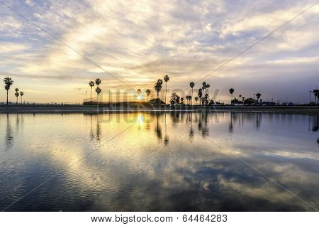 The sunrise over Sail bay in Mission Bay over the Pacific beach in San Diego California in the United States of America. A view of the palm trees reflected on the beautiful saltwater bay at sunset. poster