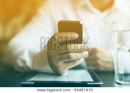 Man with smart phone in hand, blurred background, glass of wather