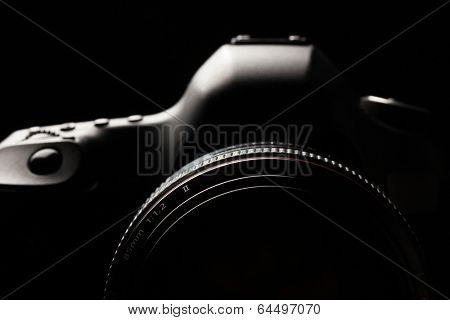 Professional modern DSLR camera low key image - Modern DSLR camera with a very wide aperture lens on