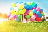 Happy birthday woman against the sky with rainbow-colored air balloons in her hands. sunny and positive energy of nature. Young beautiful girl on the grass in the park. poster