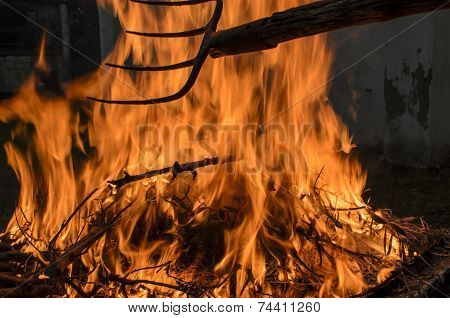 The fork moves the wood burning with high flames. poster