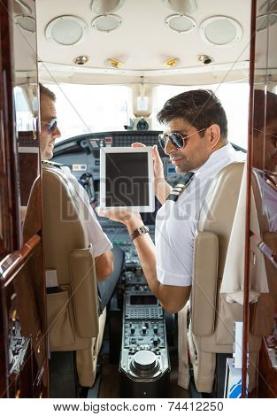 Pilot showing digital tablet to copilot in cockpit of private jet