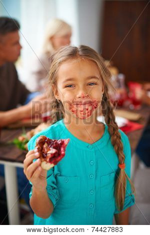 Portrait of smudgy girl eating sweet pie on background of her parents