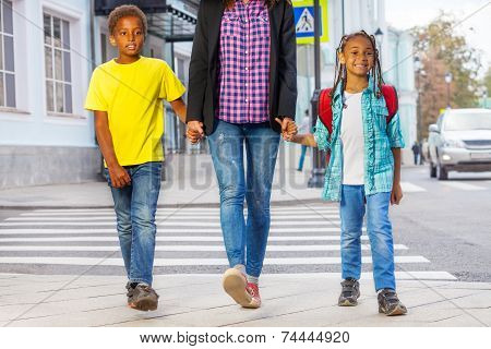 Smiling African kids with woman walk on the street