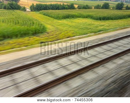 tracks and rails out in motion from a moving train. symbol photo for train ride, tempo and dynamics.