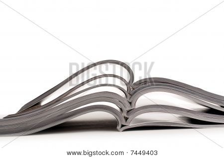 A Stack Of Open Magazines On A White Background