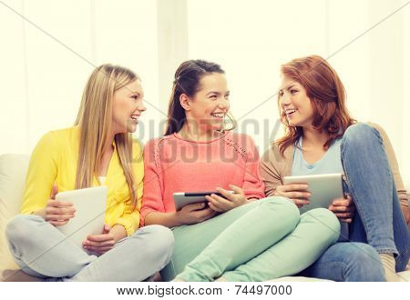 friendship, technology and internet concept - three smiling teenage girls with tablet pc computers at home