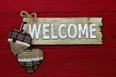 Rustic wooden welcome sign with red and green hearts hanging on antique red barn door poster
