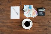 cup of coffee calculator notepad and euro money on the table poster