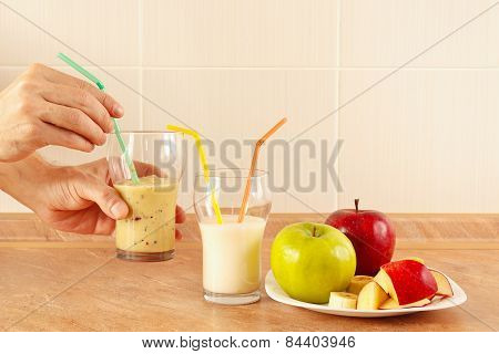Hands chef offers multifruit smoothie in glasses