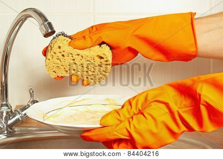 Hands in gloves with sponge and dirty dishes over the sink in kitchen