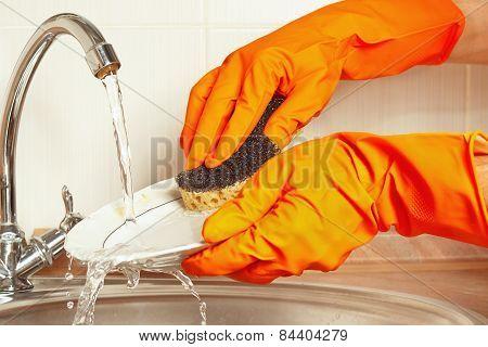 Hands in gloves wash the plate under running water in kitchen