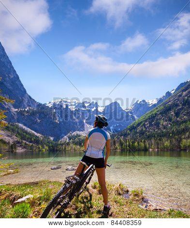 Young woman riding a bike beside Alpine lake
