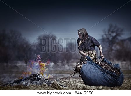 Senior Rural Woman Burning Fallen Leaves
