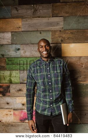 Portrait Of Happy Young Man Against Wooden Wall