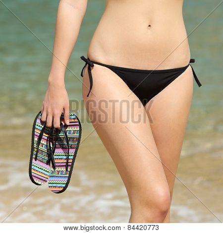 Woman Wearing Bikini Walking Holding Flip Flops In Her Hand