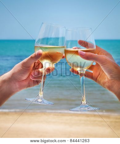 Man And Woman Clanging Wine Glasses With White Wine At Sea Background
