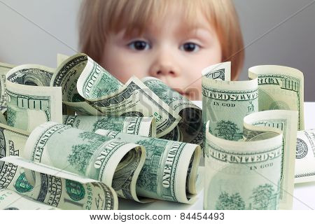 Pile Of United States Dollars And Baby On A Background