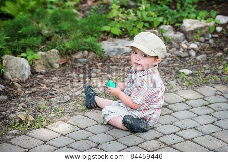 Little Boy Sits Holding A Green Easter Egg