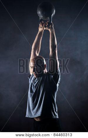 Bald charismatic athlete doing kettlebell swings.