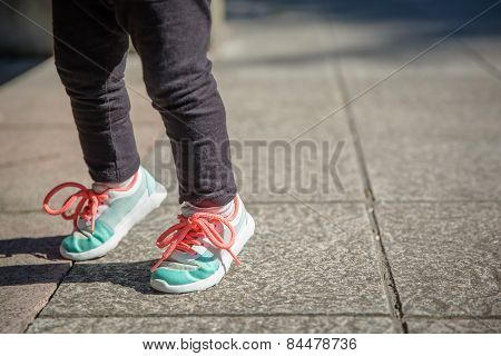 Little girl with sneakers and leggins training outdoors