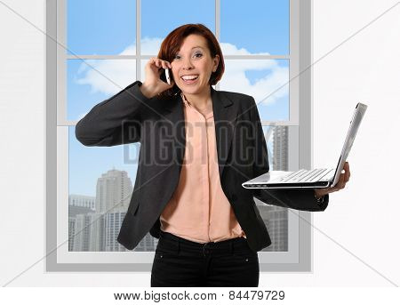Happy Business Woman With Red Hair Talking On The Mobile Cell Phone Holding Computer Laptop In Hand