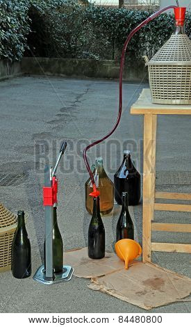 Homemade Bottling Red Wine In Glass Bottles With A Funnel