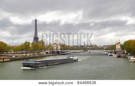 Eiffel Tower on the bank of river Seine with ship spring cloudy day