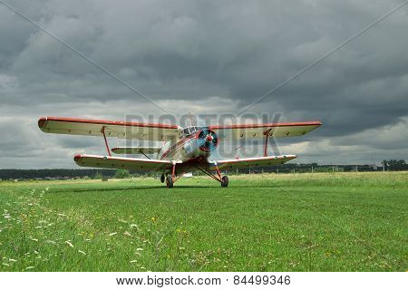 Old propeller biplane taking off from the rough airstrip with stormy clouds on the background poster