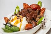 Traditional Turkish Bursa iskender kebap doner served with special red sauce and yogurt, garnished with grilled tomatoes and peppers poster