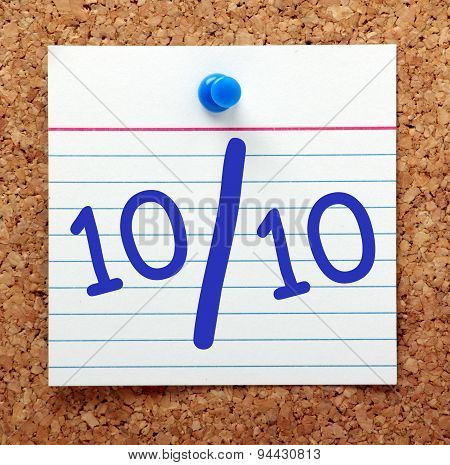 A perfect score or grade of ten out of ten in blue text on an index card pinned to a cork notice board poster