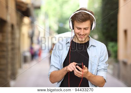 Guy Walking And Using A Smart Phone With Headphones