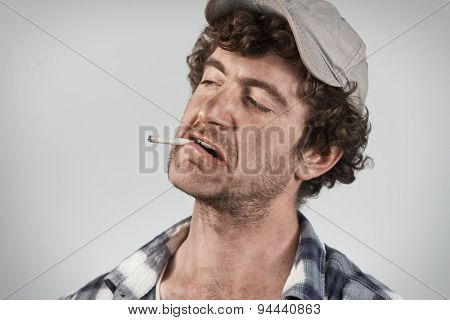 Disgusted redneck complains and grimaces while smoking a cigarette poster