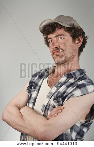 Confident redneck folds his dirty arms while smoking a cigarette poster